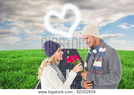 Attractive man in winter fashion offering roses to girlfriend against road on grass