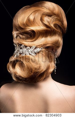 Beautiful red-haired girl in a black dress with a smooth evening haircut in the form of waves and br