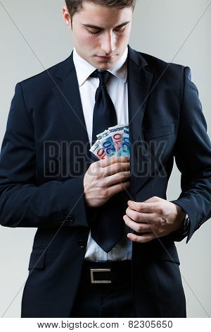 Young Man In Formalwear Putting Money In His Pocket.