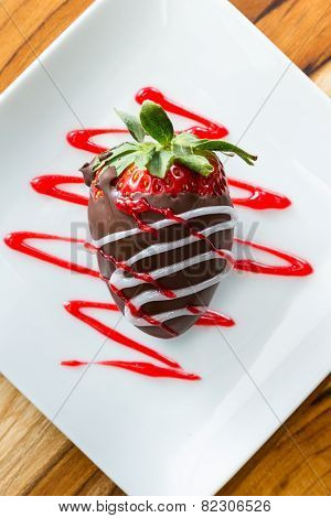Fresh Strawberry Dipped In Chocolate And Garnish With Red And White Swirls On A White Plate