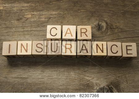 Car insurance text on a wooden background