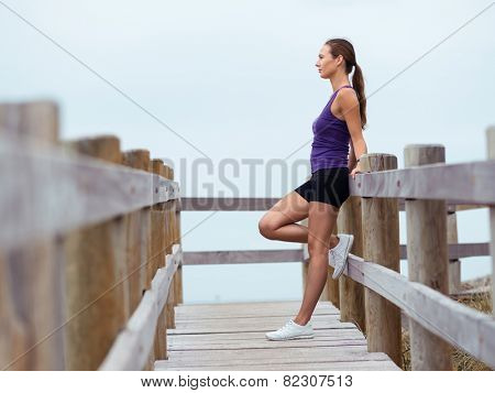 Sporty young woman standing and looking at sea