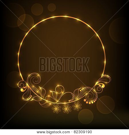 Glossy frame decorated by golden floral design on brown background.