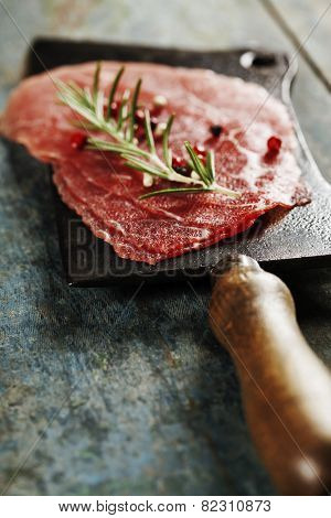 vintage cleaver and Beef Carpaccio on dark background
