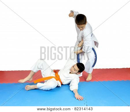 After throwing athlete in karategi  performs blow hand
