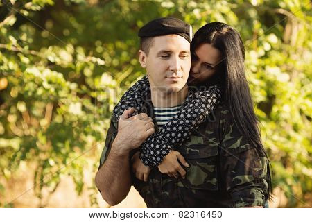 Woman and soldier in a military uniform say goodbye before a separation