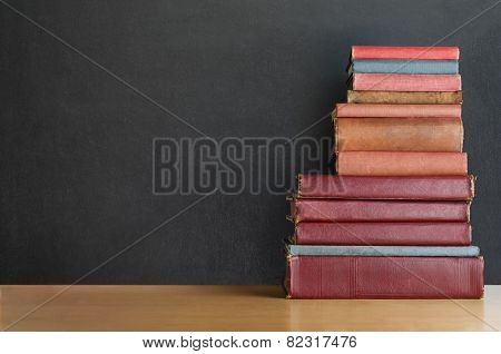 Book Stack On Desk With Chalkboard Background