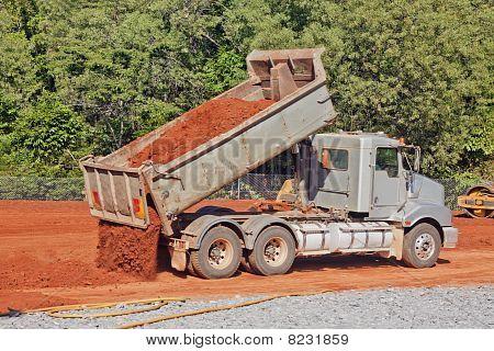 Tip Truck Dumping Dirt On A Construction Site