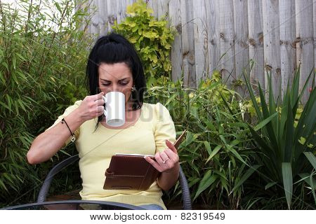 A Woman Sitting In The Garden Reading
