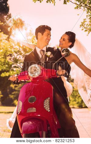 Portrait of a newlywed couple sitting on scooter in the park
