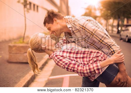 Hip romantic couple dancing in the street on a sunny day in the city