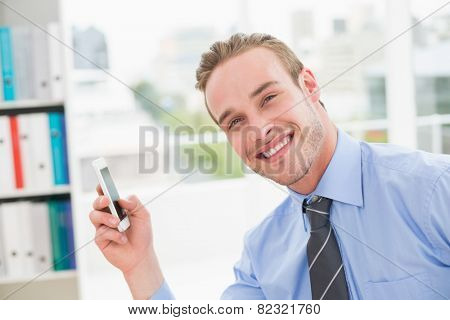Smiling businessman using smartphone in his office