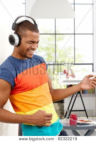 Young black man enjoying music through headphones eyes closed, pretending to play a guitar.