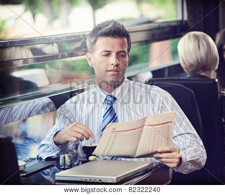 Elegant businessman traveling on luxury train, having coffee reading newspaper. vintage effect.