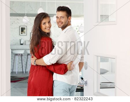 Attractive young couple embracing, looking back over shoulder in entrance door at home. Both smiling, looking at camera.