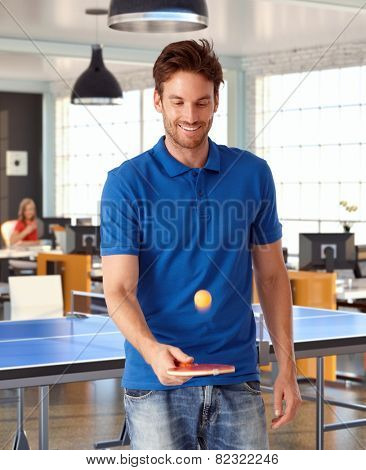 Young man playing ping pong in office, smiling.
