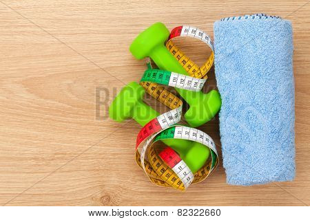 Dumbells and tape measure over wooden table with copy space. Fitness and health
