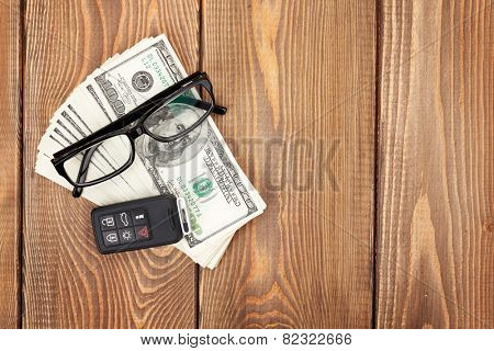Money cash, glasses and car remote key on wooden table. View from above with copy space