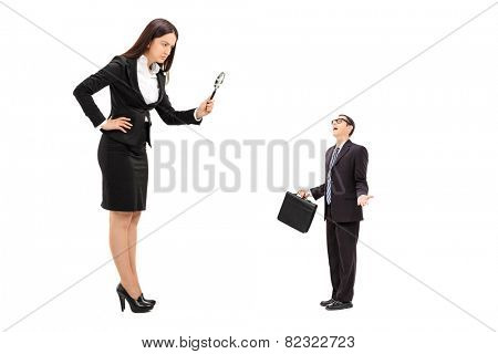 Giant businesswoman observing a tiny businessman through a magnifying glass isolated on white background