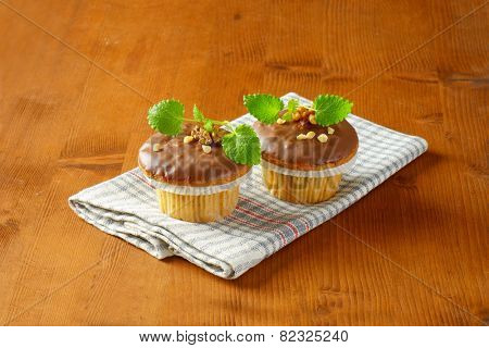 two chocolate muffins on checkered dishtowel