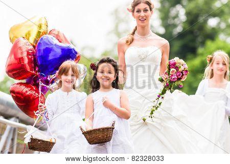 Wedding bride with flower children or bridesmaid in white dress and flower baskets