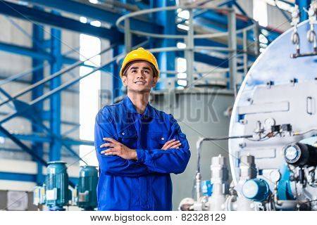 Proud Asian worker standing in production factory