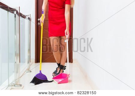 Woman or housewife cleaning up sweep floor with hand broom and shovel