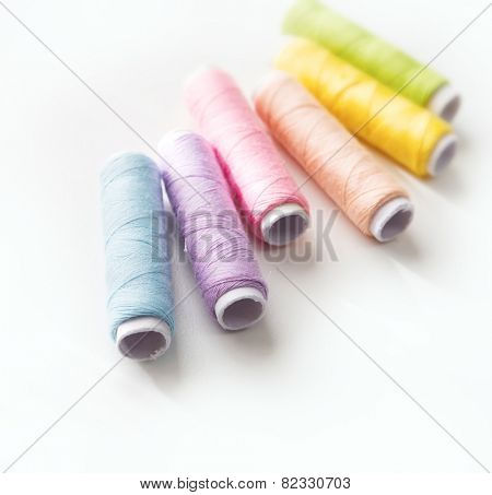 Spring colored thread spools. Light colored sewing threads on white table.
