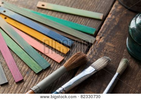 Wood color samples and brushes on an old wooden surface. Focus is on brown brush bristle.