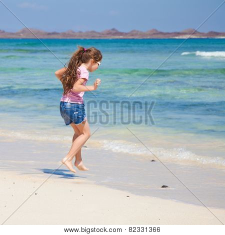 Little Girl With Long Brown Hair In Ponytail In Pink T-shirt And Denim Shorts By The Ocean