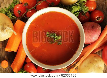 Vegetables soup surrounded by fresh vegetables on a wooden background