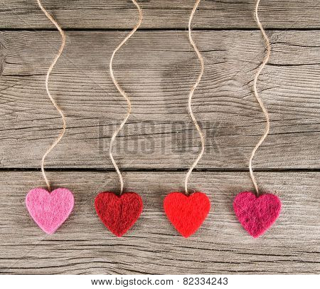 felt fabric love valentine's hearts hanging on rustic driftwood texture background with twine