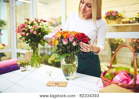 Female florist taking care of fresh flowers in the shop