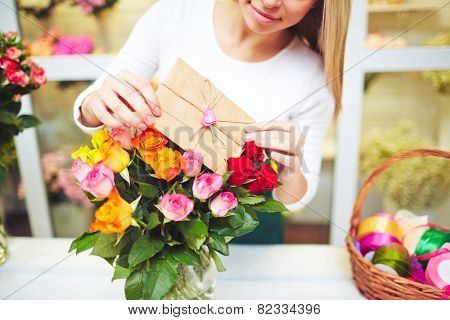 Young florist putting love note in small envelope in fresh rose bouquet