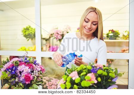 Friendly florist spraying fresh flowers in the shop