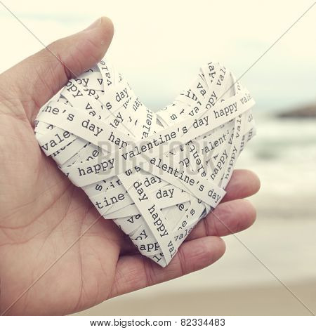 the hand of a young man holding a heart made-up with paper strips with the text happy valentines day, with a filter effect