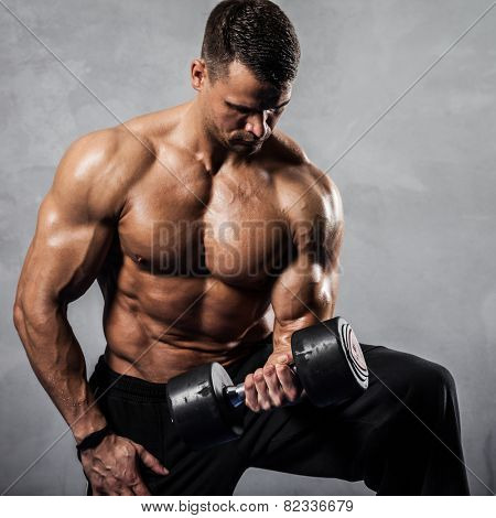 Brutal athletic man pumping up muscles with dumbbells