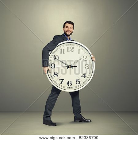 laughing businessman holding big white clock and looking at camera over dark grey background