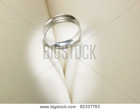 Wedding ring casting a heart-shaped shadow on the book