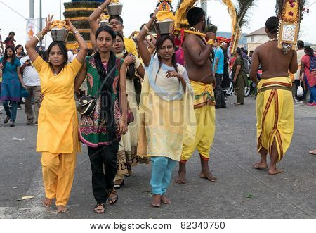 KUALA LUMPUR, MALAYSIA - FEBRUARY 3, 2015: Hindu devotees carry milk pots and kavadis walk in a procession to the Batu Caves temple on Thaipusam day, a day of thanksgiving and devotion.