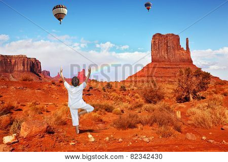 Navajo Reservation in the US. Woman in white doing yoga. Fly over the valley huge balloons