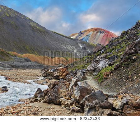 National Park Landmannalaugar in Iceland. Creek in the gorge between mountains. On the horizon - pink mountain top with turquoise stripes