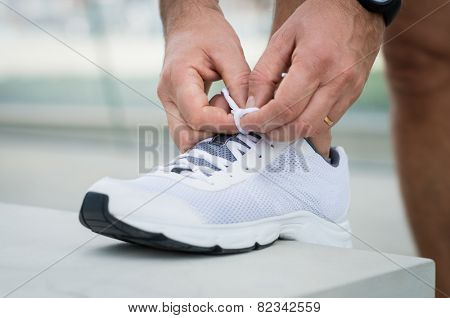 Closeup Of Male Tying Shoelace On Sneakers