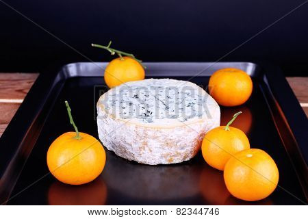 Blue cheese with oranges on metal pan and dark background