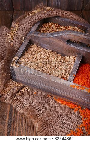 Groats in wooden box on sackcloth on wooden background