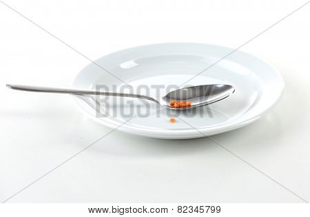 Remnants of lentils n spoon on plate with spoon isolated on white