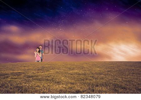 Couple hugging and holding brush against aurora night sky in purple