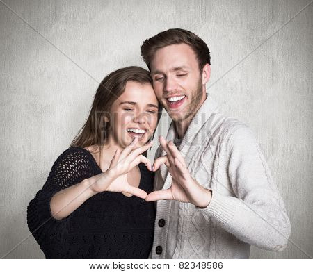 Happy couple forming heart with hands against weathered surface