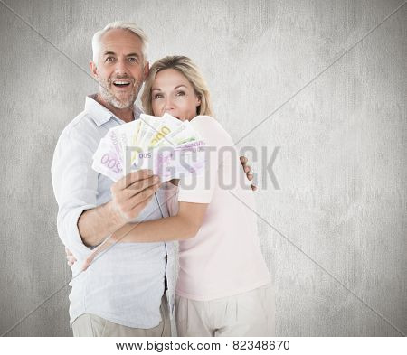 Happy couple flashing their cash against weathered surface