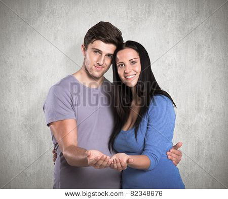Young couple holding out hands against weathered surface